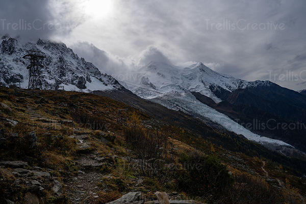 Rugged mountain hiking trail leads along the edge of Mont Blanc to the glacier