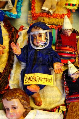 Baby Jesus figure (called Niños in Spanish) for nativity scene wearing face mask / shield and protective clothing against the...