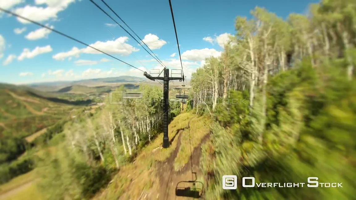 Ski lift ride time lapse down mountain in the summer using a tilt shift effect.