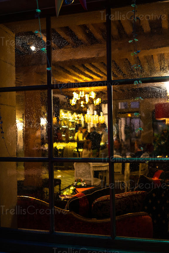 Looking into a cozy restaurant from a cold rainy night
