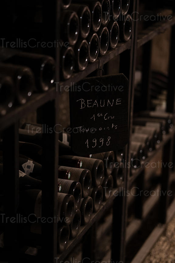 Wine cellar filled with dusty bottles of older vintage wines from Burgundy, France