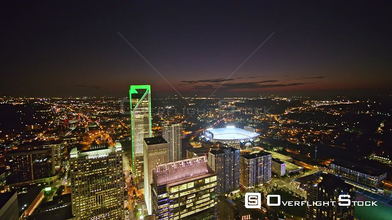 North Carolina Charlotte Aerial Flying through downtown cityscape at dusk in reverse away from stadium