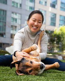 Seated Woman on Ground Pets Dog on its Side