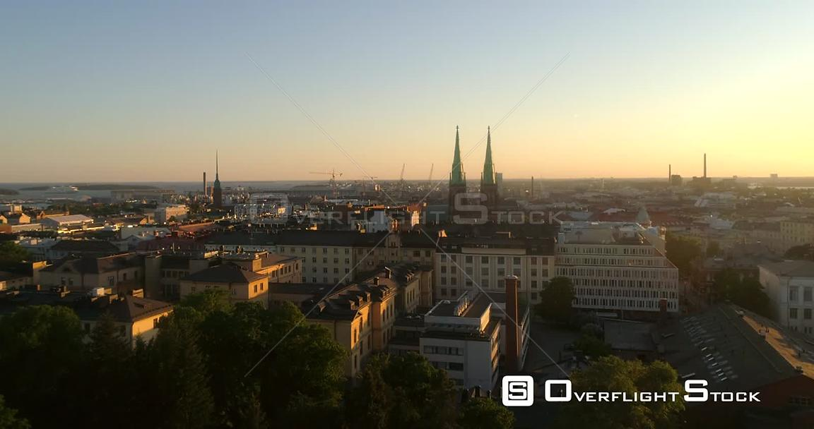 Helsinki cityscape, C4K aerial rising view of punavuori and saint johns church, in the city of Helsinki, on a sunny summer ev...