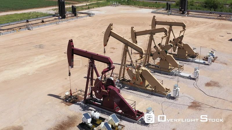 Four oil well pump jacks in a row, Brazos County, Texas, USA