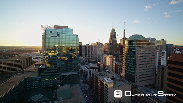 Baltimore Maryland Aerial Flying through highrise downtown cityscape into sunset