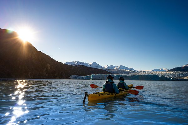 Kayaker passing floating blue ice on Lago Grey, Torres del Paine National Park, Last Hope Province, Magallanes Region, Chile,...