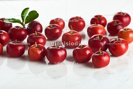 Group of acerolas on white marble background