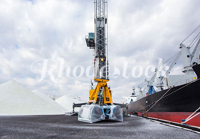 A shovel bucket on a crane rests while unloading salt from a freight ship in Providence, RI