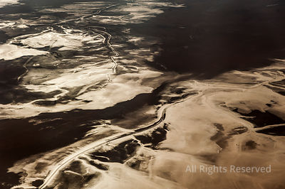 Beautiful Abstract Landscape Image of Light Reflecting on Salt Flats Taken from Airplane Window Above the Salar De Uyuni Duri...