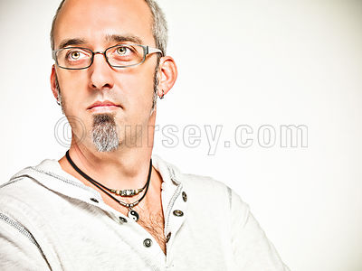 portrait of mael with salt and pepper hair, glasses, and a goatee in a white pullover shot on a white background.
