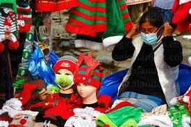 A street vendor puts on a face mask at her stall selling masks (including one with The Grinch on it) in a Christmas market, L...
