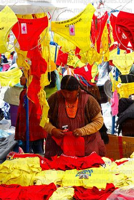 Aymara woman arranging red and yellow underwear on her stall on New Year's Eve, La Paz, Bolivia