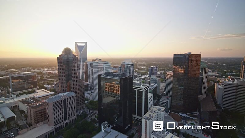 North Carolina Charlotte Aerial Flying across cityscape at sunset to panning away