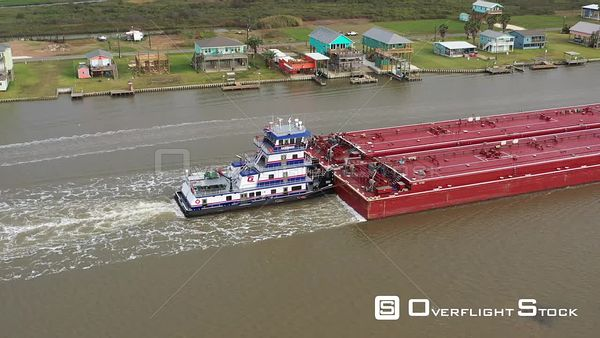 A Towboat with Barges Pass in Front of Coastal Homes, Sargent, Texas, USA