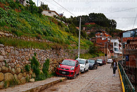 Cars parked next to Inca wall below section of Qhapaq Ñan at Paqlachapata, the start of the former Inca road to Antisuyu, Cus...