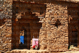 Pink wheelbarrow in doorway of south wall of Inca temple of Iñak Uyu, Moon Island, Lake Titicaca, Bolivia