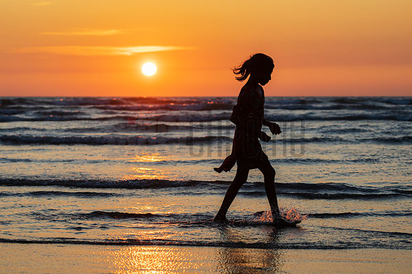 Girl Walking on the Seashore at Sunset