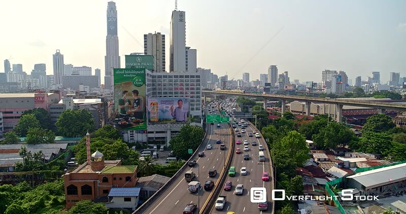 Thailand Bangkok Aerial Flying path of expressway with traffic, panning around to neighborhood view