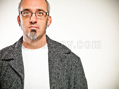 portrait of mael with salt and pepper hair, glasses, and a goatee in a white t-shirt and winter coat with hands in pocket sho...