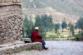 Elderly Quechua woman sitting next to irrigation channel, Ollantaytambo, Sacred Valley, Peru