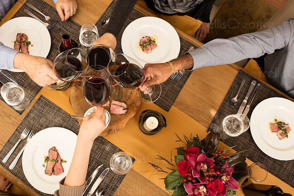 Aerial view of four people at a celebration meal, clinking wine glasses.