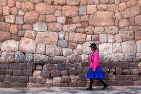 Quechua woman walking past Inca stone wall, Plaza San Pedro , Cusco , Peru