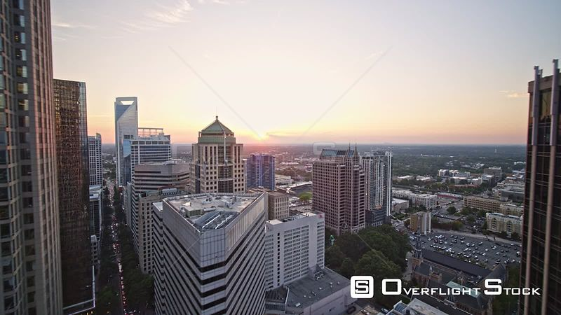 North Carolina Charlotte Aerial Flying backwards through downtown to landscape view at sunset