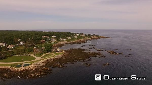 Flying low over coastline homes panning. Maine