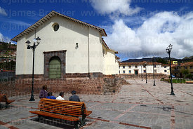 People sitting on bench  in Plaza Santa Ana and Santa Ana church, Cusco, Peru