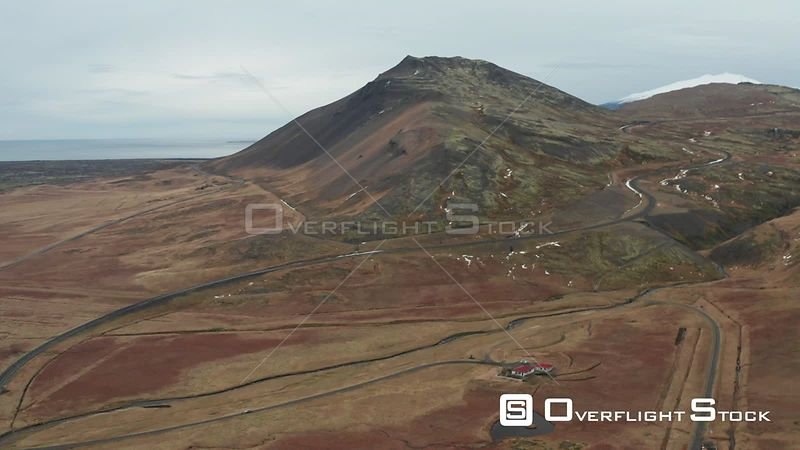 Flying Towards a Mountain Over Roads and a Small House in Iceland.