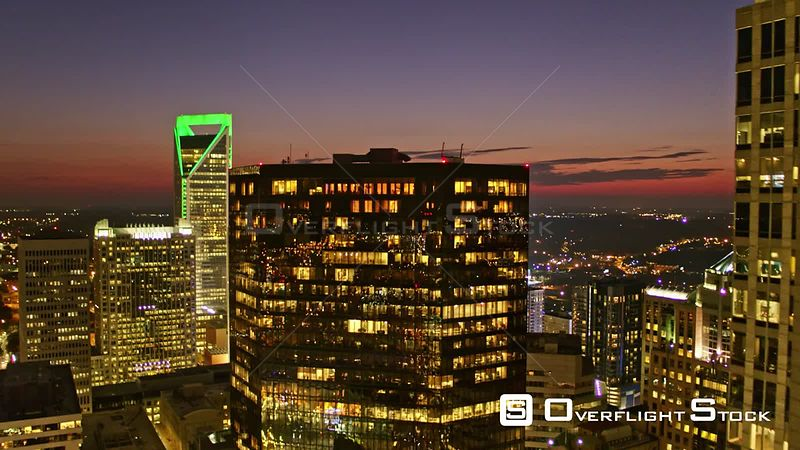 North Carolina Charlotte Aerial Flying backwards through downtown cityscape with sunset sky