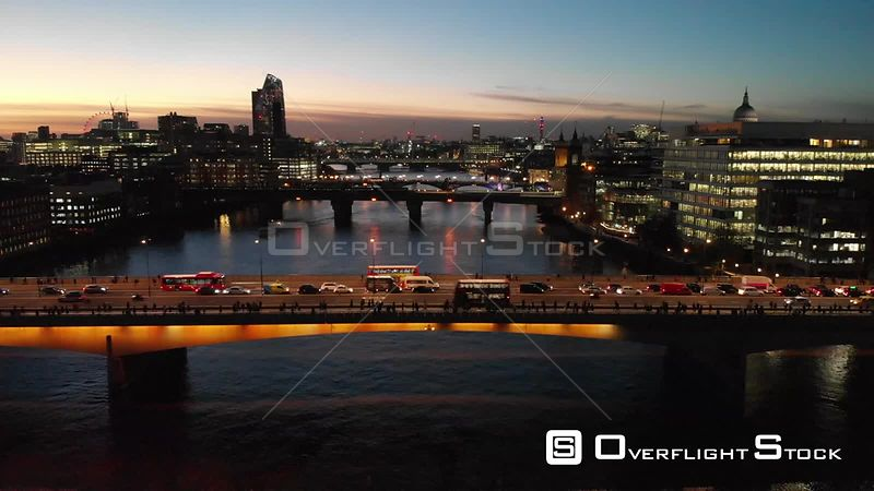 Cars driving on London Bridge, filmed by drone in autumn, at dusk, London, United Kingdom