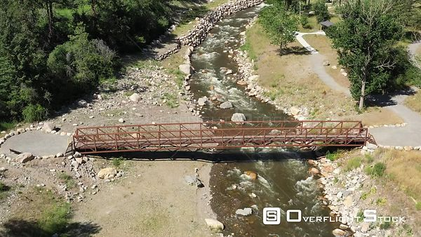 Pedestrian bridge over a rushing mountain river, Estes Park, Colorado, USA