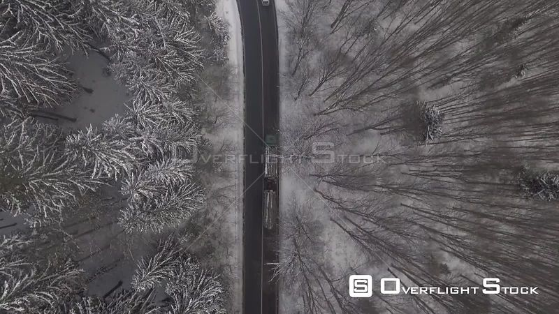 Tracking of a truck driving on a mountain serpentine road through a forest winter time. Romania