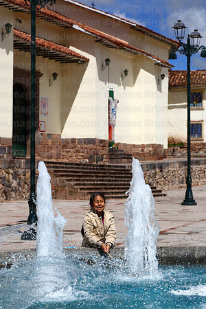 Girl playing with water in fountain in Plaza Santa Ana, Santa Ana church behind, Cusco, Peru