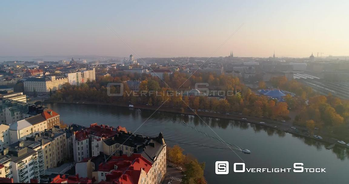 Autumn cityscape, C4k aerial, dolly, drone shot, of the Kaisaniemi park, the railway station and the cathedral, a boat on too...