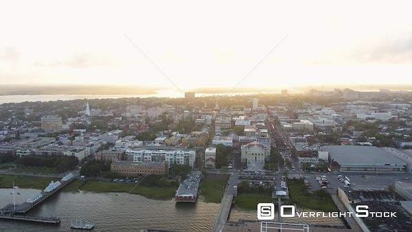 South Carolina Charleston Aerial Flying low to high backwards around French Quarter and port with city view at sunset