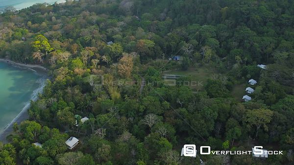 Flying low over eco lodging in jungle forests looking down. Costa Rica