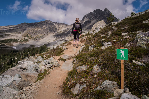 Woman backpacking up steep rocky trail, Blackcomb Mountain, Whistler, Canada.
