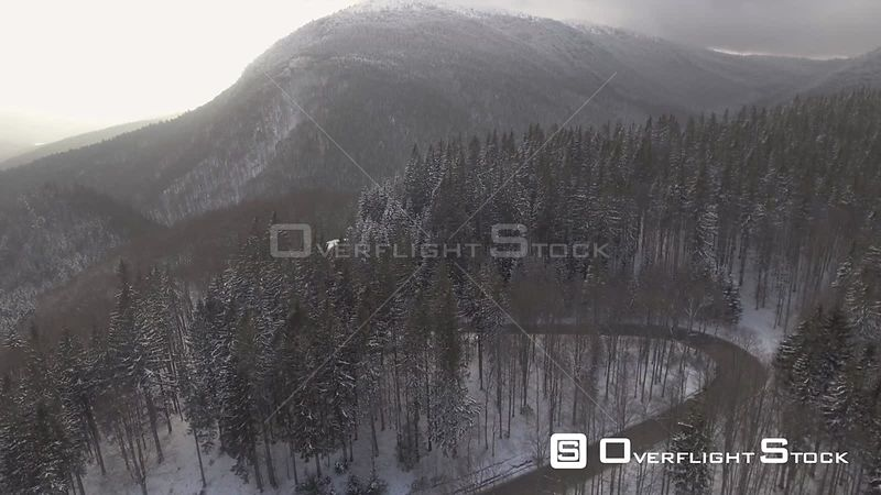 Mountain serpentine road through a forest winter time. Romania