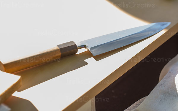 Close up of a chef's knife on a white table.