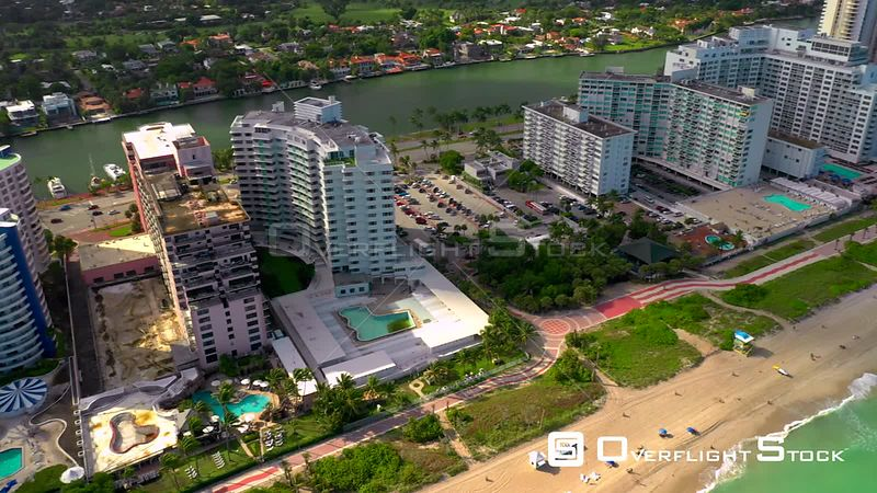 Aerial pan and tilt up reveal Miami Beach oceanfront luxury real estate condo hotels 4k