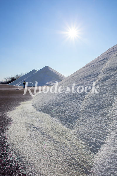 A man examines tall piles of road salt