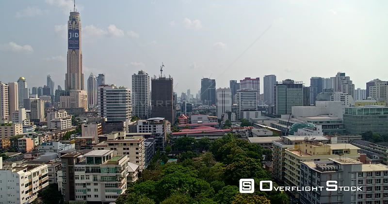 Thailand Bangkok Aerial Flying very low through Ratchathewi and Pathum Wan districts starting at park