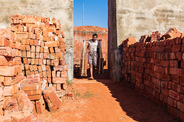 Portrait of a Brick Worker Carrying Bricks