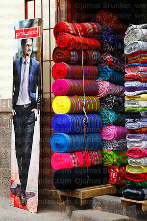 Banner of male fashion model outside shop selling rolls of fabric, Cusco, Peru