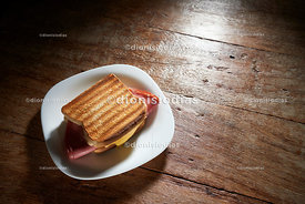Bologna and cheese hot sandwiches at a rustic table.