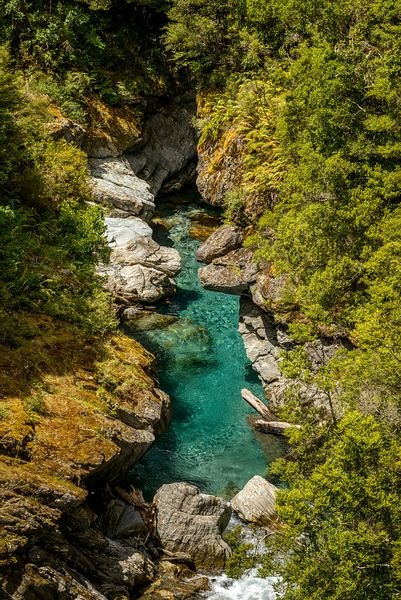 Clear blue river waters in stream over Haast Pass, New Zealand.