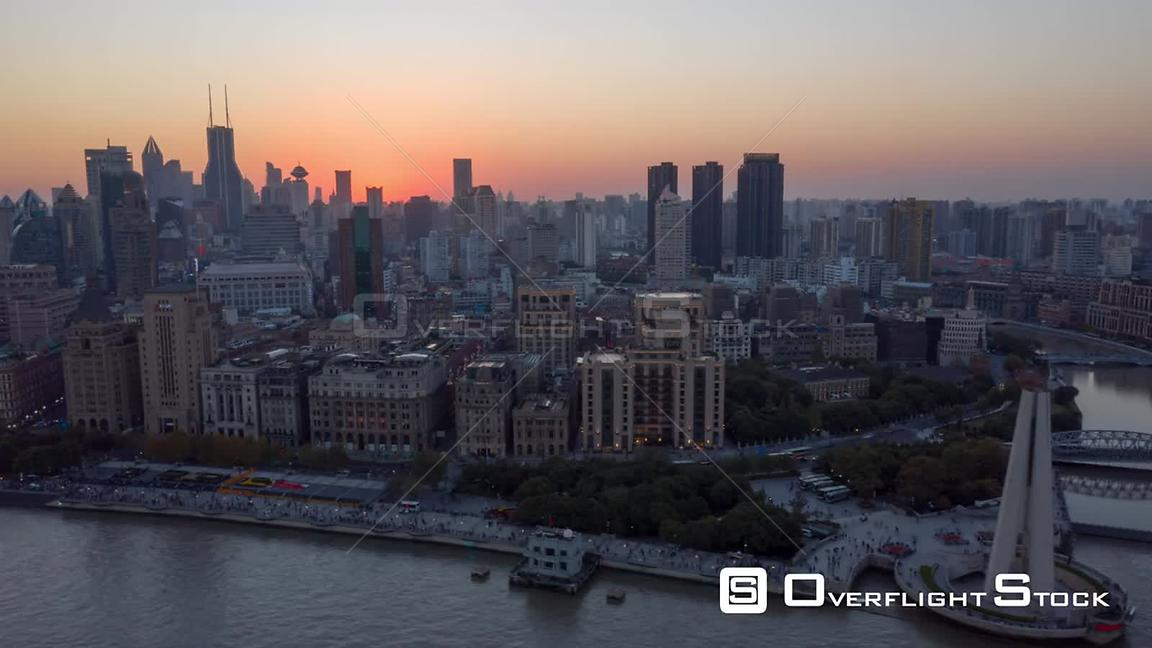 China Shanghai Aerial Hyperlapse flying low over Huangpu river with waterfront view with sun setting in backdrop